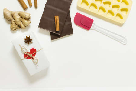 Valentine day cooking, gift preparation, recipe presentation arrangement with a present, chocolate, herbs and empty blank space.