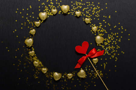 Romantic Valentines day wreath with golden glitter hearts and golden stars with red heart on wooden stick with red bow on black background.