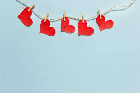 Valentines day simple greeting card with five hanging red fabric hearts pinned to a rough rope packthread on blue background.