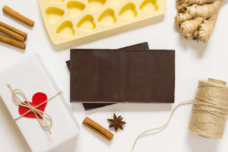 Valentine day cooking scene, recepie mock up and preparation for celebration. Photo with chocolate, herbs, cinnamon, chocolate mold, packthread rope and present with heart.