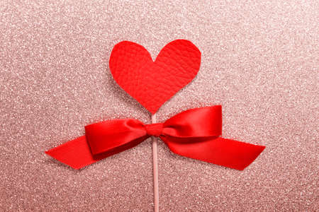 Valentine day greeting card with red fabric heart on pink glitter background. Stockfoto