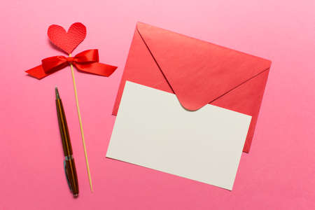Valentine day greeting card with pink envelope and white empty card, Parker pen and red heart on wooden stick. Stockfoto