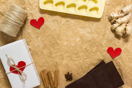 Preparation for Valentines day. Arrangement of cooking items, chocolate and herbs on craft paper. Photo with copy blank space.