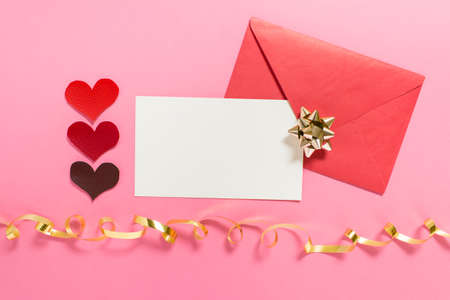 Valentine day mock up with red hearts, golden bows, pink envelope and white message card on pink background.