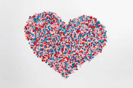 Large heart made of red blue pink paper confetti isolated on white background.