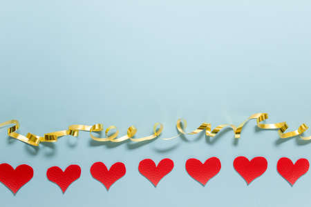 Valentine day simple greeting card with golden ribbon and row of many fabric hearts on blue background. Photo with copy blank space.