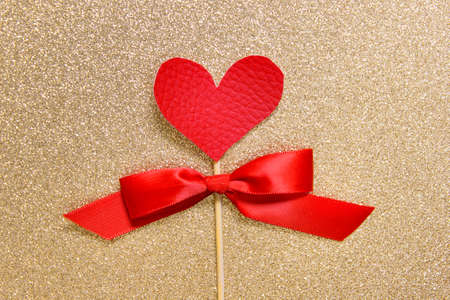 Simple minimalistic Valentine day greeting card with red heart and red satin bow on wooden stick on golden glitter backgound.