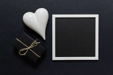 Minimalistic composition for Valentines day with white frame, white porcelain heart, gift box on black background.