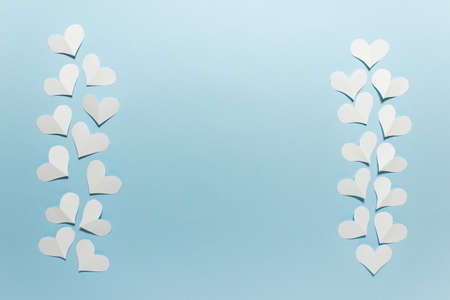 Two vertical rows of white folded origami paper hearts on blue paper background. Photo with copy blank space. Stockfoto