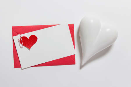 Valentines, Mothers, Fathers day greeting card mock up with pink envelope, blank message card and white porcelain heart on white background.