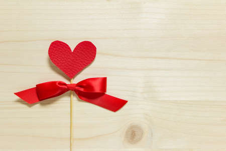 Handmade Valentine day greeting card template with red fabric heart on wooden stick with red satin bow on wooden background. Photo with copy blank space.