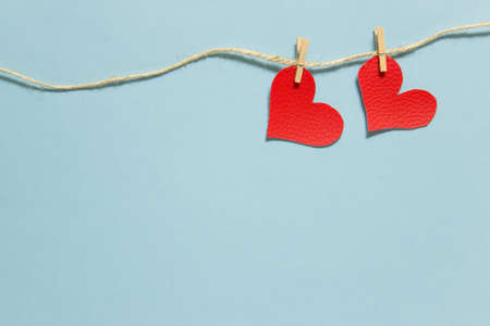 Valentine day message background template with copy blank space and two red hearts pinned to a rope.