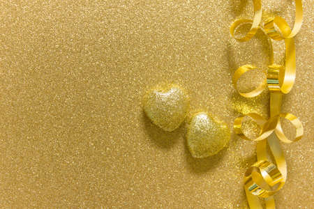 Simple greeting card with two golden hearts and golden festive ribbon on golden glitter sparkling background. Photo with copy blank space.