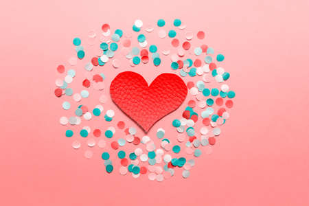 Red large fabric textile heart on pink background with blue white pink paper confetti.