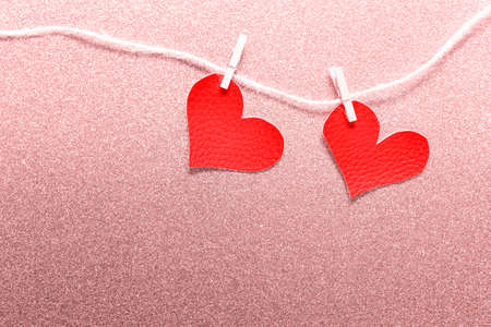 Two large fabric hearts pinned to packthread on pink background. Photo with copy blank space.