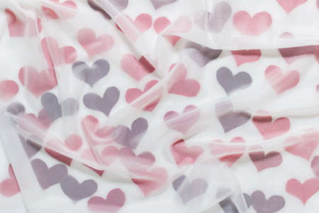 Abstract Valentines day celebration cheerful background with many red fabric hearts covered with transparent white cloth. Stockfoto