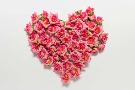 Romantic Valentines day greeting card with heart made of pink roses on white background.