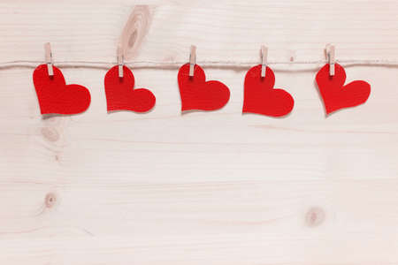 Five red textured Valentine hearts pinned to pack thread on wooden background.