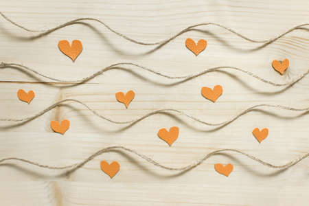Abstract Valentine day pattern with wavy rough rope packthread on wooden background with small yellow hearts.