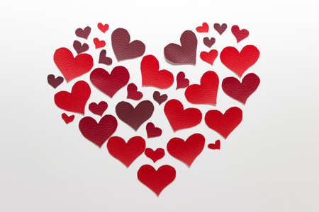 Simple Valentines day composition big heart made of red hand cut fabric hearts on white background.