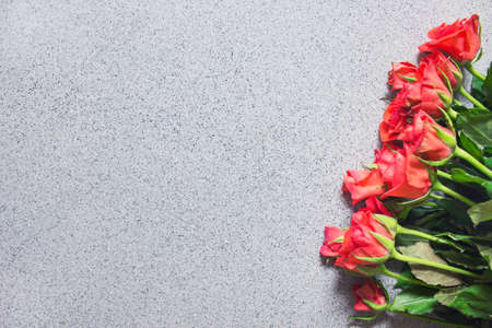 Bouquet of small red roses for Valentine day, birthday or any greeting celebration on stone like background. Photo with copy blank space. Stockfoto