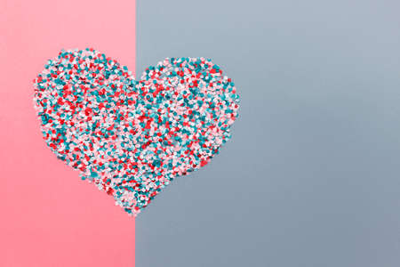 Large heart made of many paper colorful confetti on double colored pink and blue background. Photo with copy blank space.