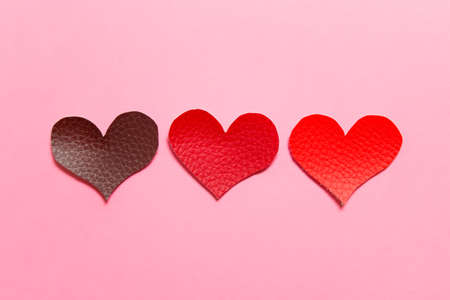 Valentine day greeting card with three red fabric textile texture hearts on pink background. Stockfoto