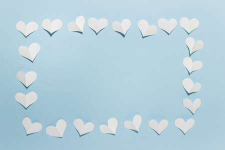 Greeting card with white folded paper hearts on blue background arranged in a frame. Photo with copy blank space.