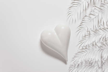 Valentines, Mothers, Fathers day greeting card with one single porcelain heart and handmade hand cut white paper leaves on white background. Photo with copy blank space. Stockfoto