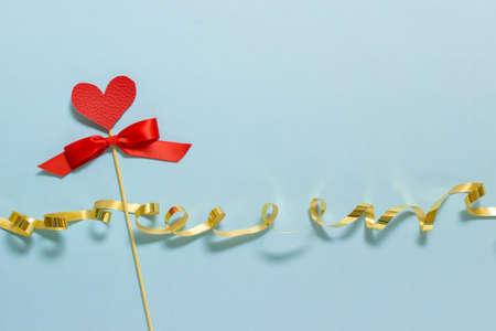 Valentines day greeting card with copy blank space and red fabric heart on wooden stick and red satin bow with golden festive ribbon on blue background.