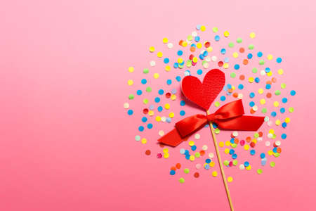 Valentine day greeting card with fabric heart on a wooden stick with red satin bow on pink background with colorful confetti. Photo with copy blank space.