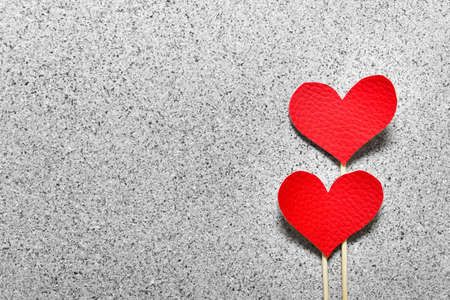 Two red fabric cloth hearts on wooden sticks on gray stone like texture background. Photo with copy blank space.