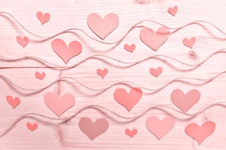 Valentine day pattern with hearts arranged on wooden background with wavy rope tinted with pink color.