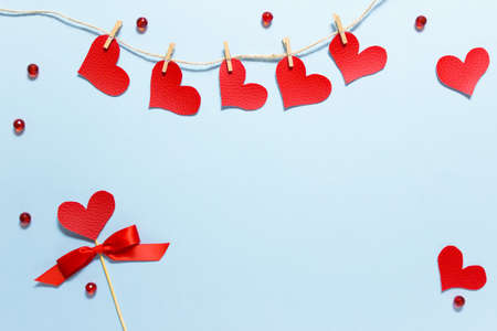 Valentine day greeting card with copy blank space and red decorative elements fabric hearts pinned to rope, crystals and bow on wooden stick on blue background. Stockfoto