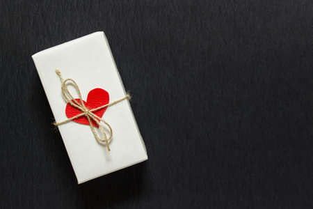 Present gift box with red fabric heart, white wrapping paper and bow made with packthread string on black background. Photo with copy blank space. Stockfoto
