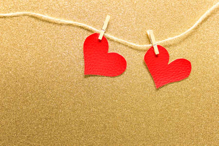 Two large fabric hearts pinned to packthread on golden glitter background. Photo with copy blank space.