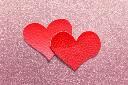 Two large fabric textile red hearts on pink glitter sparkling background. Stockfoto