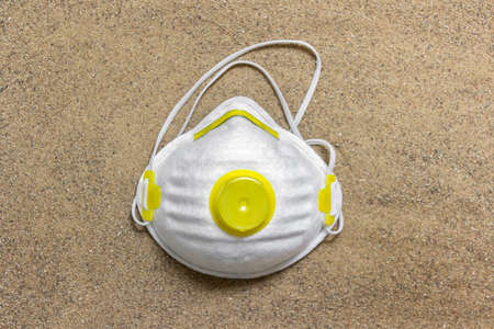 Facial protective mask lying on sand surface. Concept idea of protecting lungs from breathing in small particle dust. Фото со стока - 139888243