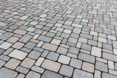 Texture of pathway pavement covered with rock bricks.