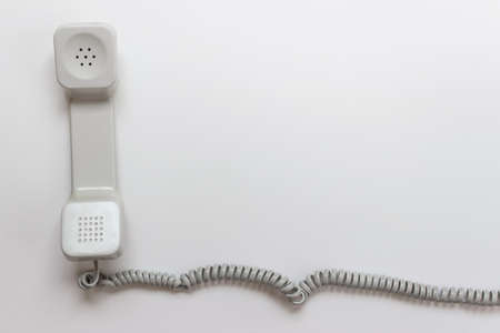 White vintage telephone phone handset with coil cable on white background. Photo with copy blank empty space.