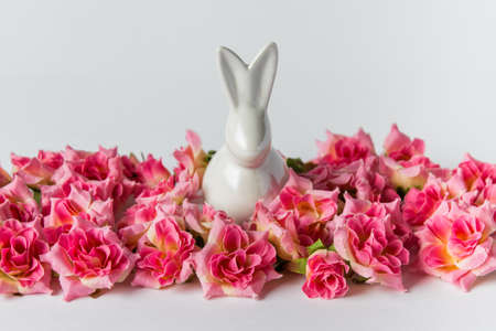 Decorative Eaester greeting card with white porcelain Easter bunny sitting in pink roses on white background.