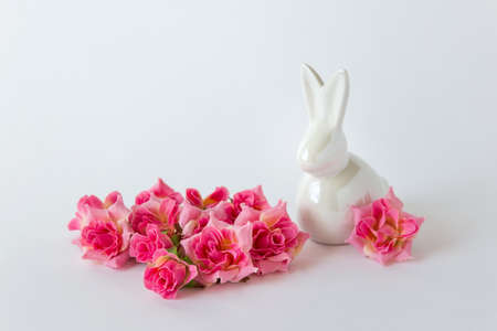 Easter bunny figurine rabbit decor with pink roses on white background. Stock Photo