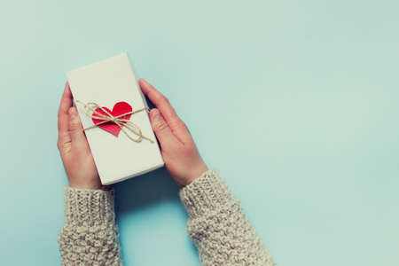 Female hands holding a present with red heart and a bow of packthread. Thank you for greeting card with copy blank space.