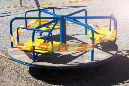 Merry-go-round carousel playground for kids with biohazard forbidden STOP tape ribbon during COVID-19 quarantine on a sunny day.
