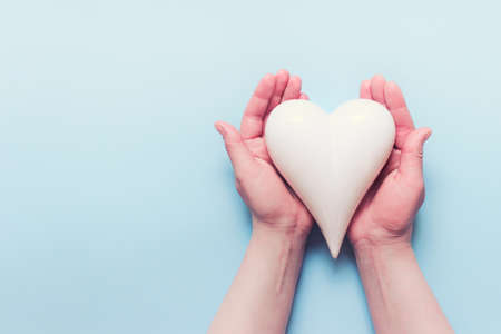 Female hands holding white porcelein heart on blue backgound. Photo with copy blank space.