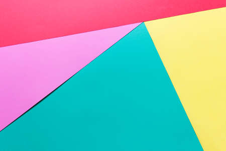 Layers of colored yellow pink mint green paper. Photo with copy blank space for text art presentation.
