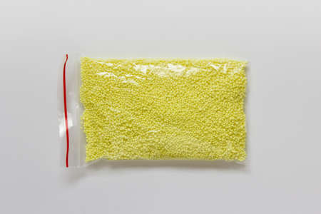 Closeup of packaged sulfur in a plastic on white background. Reklamní fotografie