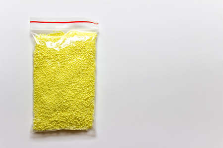 Granules of yellow sulfur chemical element in a plastic bag on white background. Photo with copy blank space.