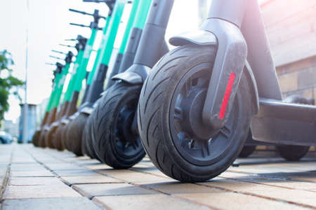 Close Up on a wheel of worn electric city scooter standing in a row with scratches. Stockfoto