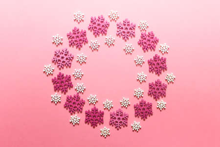 Decorative Christmas wreath made of wooden red and white snowflakes on pink background. 免版税图像
